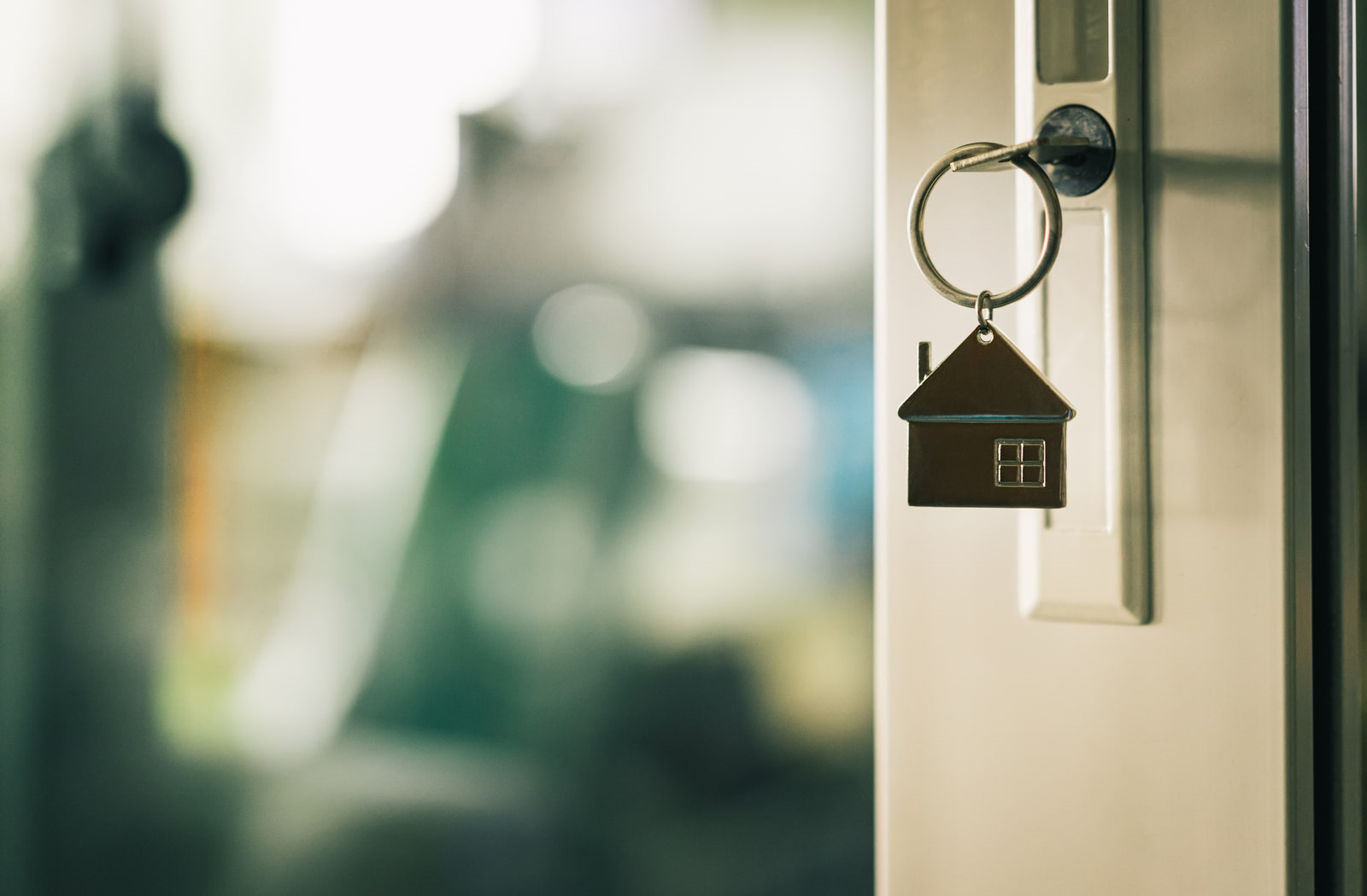 Key on a house-shaped key chain hanging in the open door of a newly mortgaged home