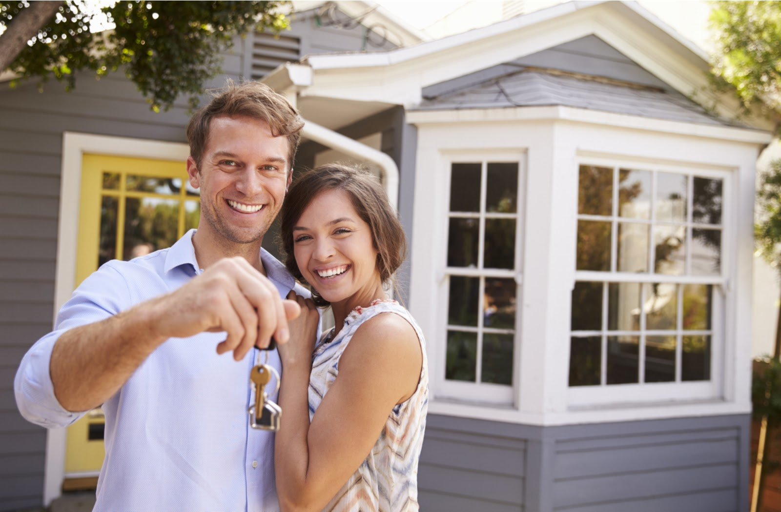 A couple standing in front of a new home they purchased holding the house keys in their hand
