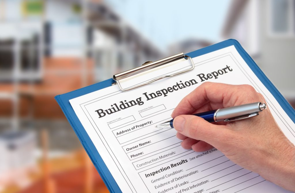 A close up of somebody ready to fill out a building inspection report for someone preparing to buy a home