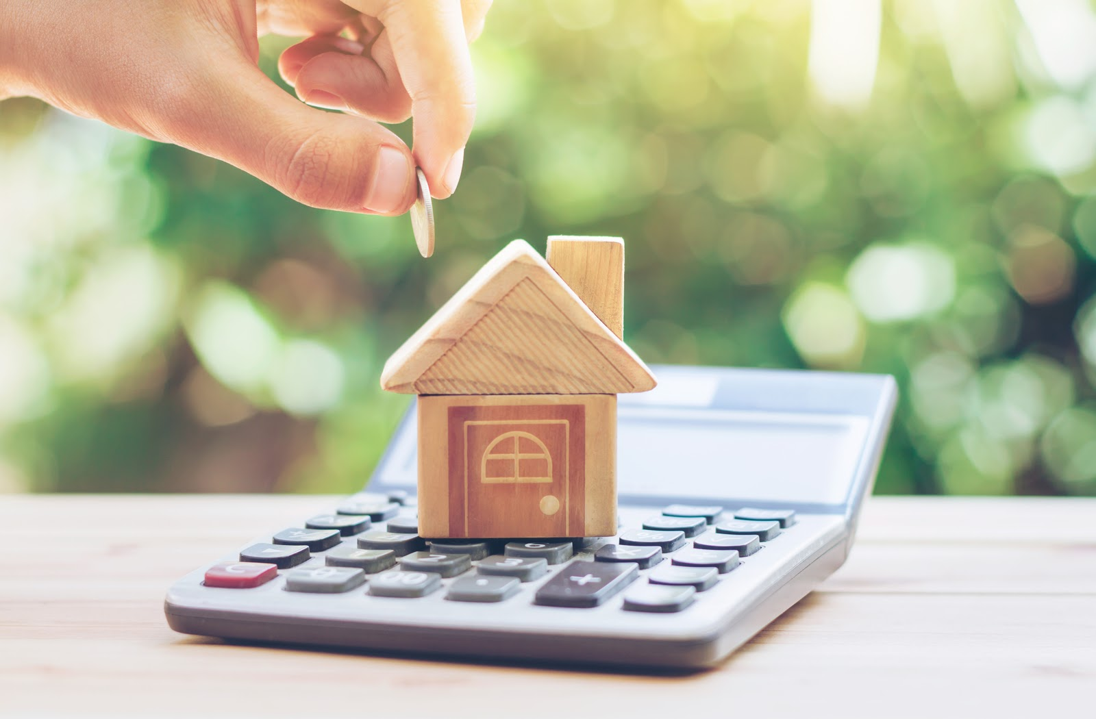 A small house sitting on the face of a calculator with a hand reaching towards it with money deciding what mortgage is best