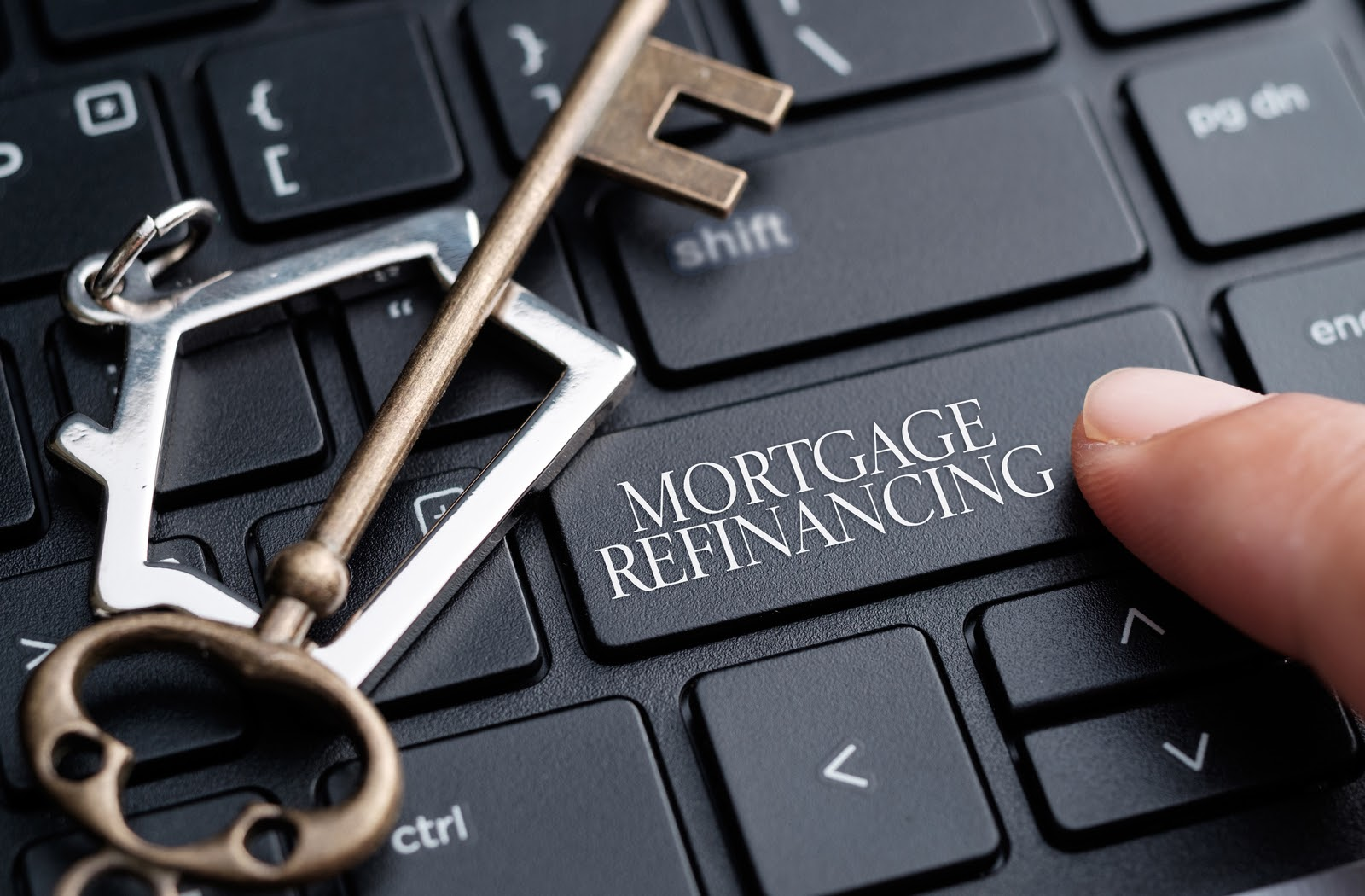 Closeup of a finger on keyboard with the words mortgage refinancing on one of the keys