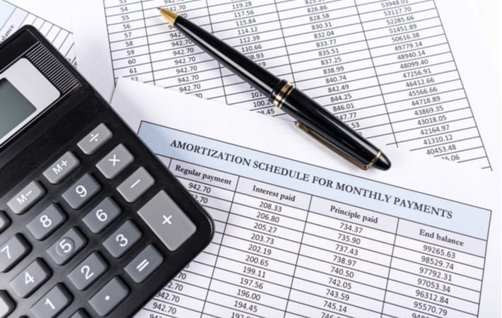 Amortization schedule documents with a calculator and a pen laying on top
