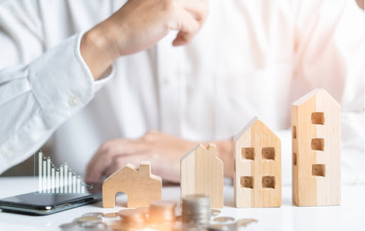 Small model houses and coins laying in front of a person attempting to calculate how much they need for a mortgage down payment